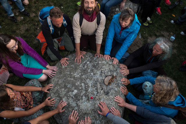 Revellers touch a stone and chant in the stone circle as they celebrate the pagan festival of Summer Solstice at Stonehenge in Wiltshire, southern England on June 21, 2017. The festival, which dates back thousands of years, celebrates the longest day of the year when the sun is at its maximum elevation. Modern druids and people gather at the landmark Stonehenge every year to see the sun rise on the first morning of summer. (Photo by  Chris J. Ratcliffe/AFP Photo)