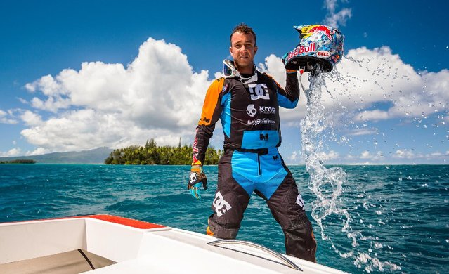 In this April, 2015, photo provided by DC Shoes, daredevil Robbie Maddison poses during a break from his latest stunt, riding his motorcycle across waves in Tahiti, French Polynesia, using ski-like devices on his wheels. (Photo by Garth Milan/DC Shoes via AP Photo)