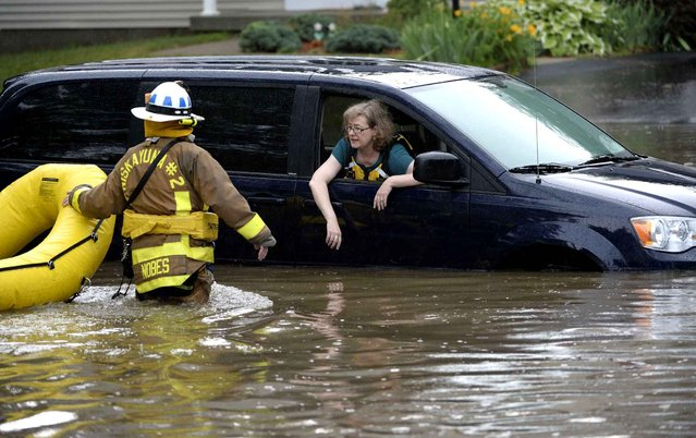 A Niskayuna, N.Y., firefighter returns for the second of two people trapped in a vehicle in floodwaters Wednesday afternoon, July 2, 2014, in Niskayuna. Several roads and highways have been closed by flooding and four highway department workers have been hurt by lightning as severe thunderstorms rolled through eastern New York, bringing torrential downpours and high winds. (Photo by Skip Dickstein/AP Photo/The Times Union)