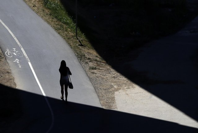 A girl walks through a shadow under the Ada bridge in Belgrade, Serbia, Tuesday, July 21, 2015. (Photo by Darko Vojinovic/AP Photo)