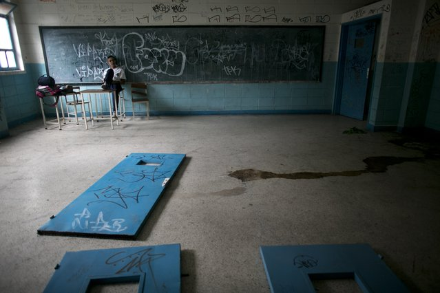 In this June 1, 2016 photo, a student sits on a teacher's desk inside what was once a classroom, where doors lay on the floor as well as urine, at a public high school in Caracas, Venezuela. The social and economic chaos stalking Venezuela is ripping apart its once-enviable school system, robbing poor students of what would otherwise be their best chance to escape lives fast becoming unbearable. (Photo by Ariana Cubillos/AP Photo)