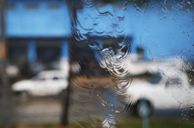 """Rain pours down the window of a media bus enroute to the Pernambuco arena in Recife June 25, 2014. In a project called """"On The Sidelines"""" Reuters photographers share pictures showing their own quirky and creative view of the 2014 World Cup in Brazil. (Photo by Brian Snyder/Reuters)"""