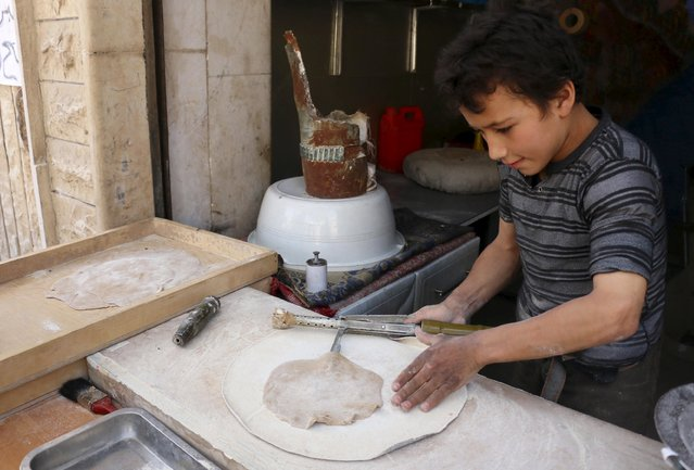 A boy uses remnants of ordnance as he prepares dough inside Abu Khaled's shop in the Douma neighborhood of Damascus April 28, 2015. (Photo by Amer Almohibany/Reuters)