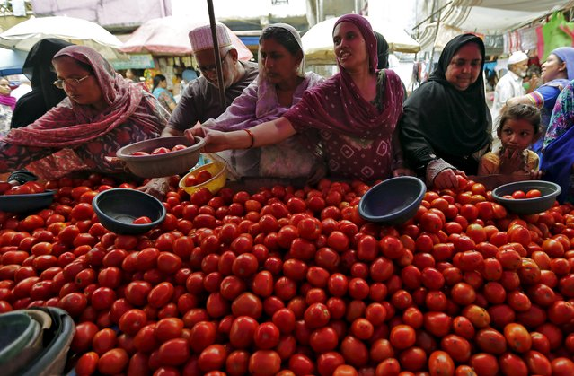 Local residents buy tomatoes from a roadside vegetable market in Ahmedabad, India, August 7, 2015. Entrenched expectations of high inflation in India are feeding into higher wages and other prices, which could tie India's central bank governor Raghuram Rajan's hands even as he faces growing pressure to cut interest rates for a fourth time this year to help a patchy economy. (Photo by Amit Dave/Reuters)
