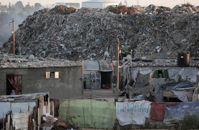 In this Monday, June 20, 2016 photo, piles of garbage surround el-Zohor slum, on the outskirts of Khan Younis refugee camp, southern Gaza Strip. (Photo by Khalil Hamra/AP Photo)