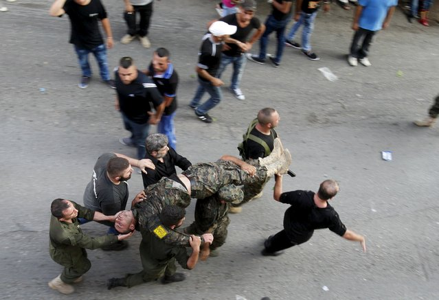 Lebanon's Hezbollah members and supporters carry a man that fainted during the funeral of his friend, Hezbollah fighter Ali Manana, in Sarafand, southern Lebanon August 11, 2015. Manana was killed during what activists said were clashes between Hezbollah fighters alongside the army of Syria's President Bashar al-Assad against Syrian Rebels in Syria. (Photo by Ali Hashisho/Reuters)