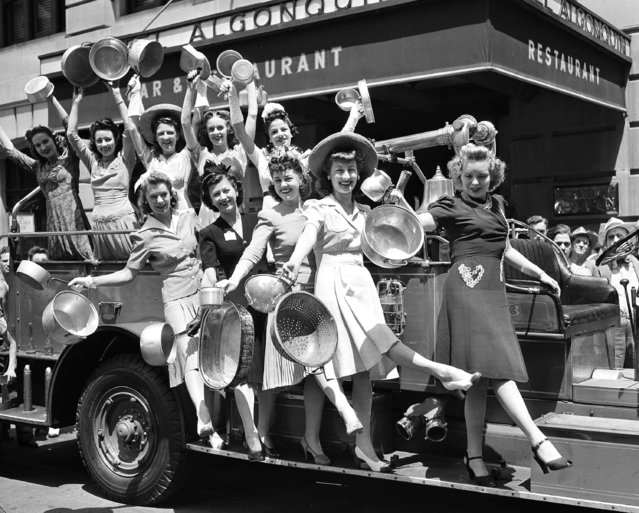 """A chorus girl """"Aluminum-Blitz"""" squad, organized to collect aluminum pots and pans for the opening of the national defense aluminum collection in New York, July 21, 1941, cheers the fire engine they used for transportation in making their around of the Times Square sector. (Photo by AP Photo)"""
