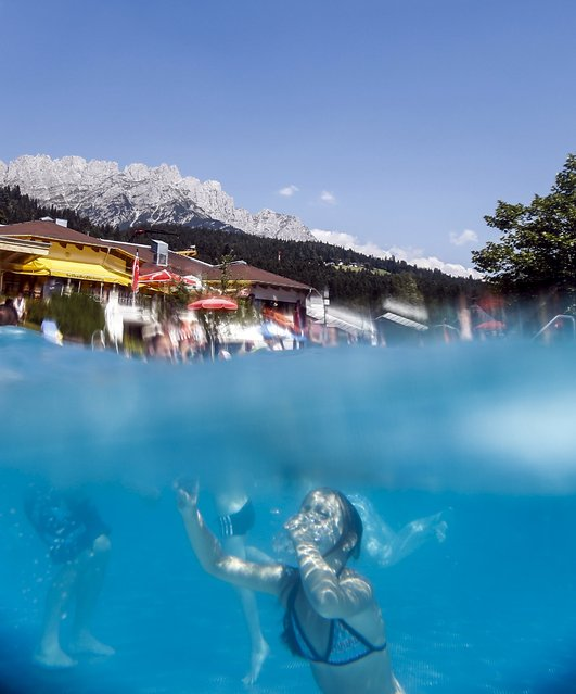 People swim in a pool on a hot summer day in the western Austrian village of Ellmau, August 12, 2015. (Photo by Dominic Ebenbichler/Reuters)