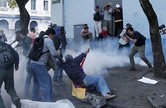 Demonstrators fall to the floor during clashes with police in Quito, Ecuador, August 13, 2015. (Photo by Guillermo Granja/Reuters)