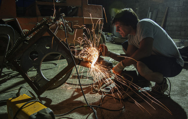 "Danilo Baletic, 22, performs last minute work on scrap metal parts for his sculpture at junkyard in Podgorica, July 22, 2014. Baletic makes sculptures of his childhood cartoon heroes, ""Transformers"", from scrap metal. In the last two years he has made seven ""Transformers"" sculptures that are placed on the streets of Montenegro's capital Podgorica as part of an exhibition called ""Transformers defending Podgorica"". (Photo by Stevo Vasiljevic/Reuters)"