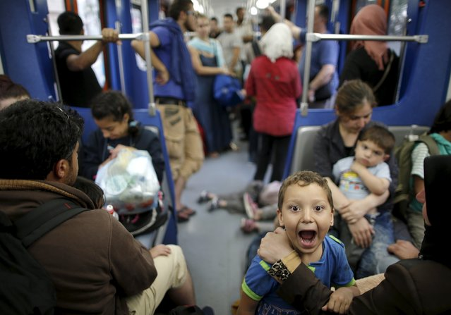 """A Syrian refugee boy reacts as he rides a Metro with relatives to central Athens after disembarking from a Greek ferry arriving from the island of Kos in the port of Piraeus, Greece, August 15, 2015. United Nations refugee agency (UNHCR) called on Greece to take control of the """"total chaos"""" on Mediterranean islands, where thousands of migrants have landed. About 124,000 have arrived this year by sea, many via Turkey, according to Vincent Cochetel, UNHCR director for Europe. (Photo by Christian Hartmann/Reuters)"""