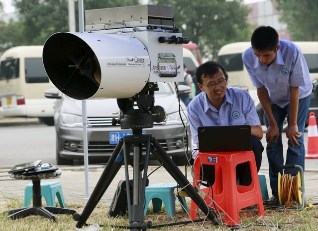 Engineers of Tianjin environmental monitoring center use a device to check the level of hydrogen cyanide present in the air at a monitoring station observing environmental pollution located within a 3-km (2-mile) exclusion zone from last week's explosion site in Binhai new district in Tianjin, China, August 18, 2015. The explosions late last Wednesday in Tianjin, the world's 10th-busiest port in China's industrial northeast, forced the evacuation of thousands of people after toxic chemicals were detected in the air. (Photo by Kim Kyung-Hoon/Reuters)