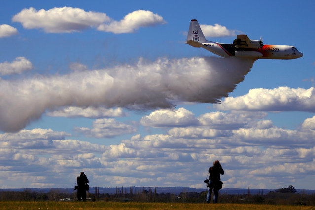 "Photographers take photographs of the Large Air Tanker (LAT) C-130 Hercules, also known as ""Thor"", as it drops a load of around 15,000 litres during a display by the Rural Fire Service ahead of the bushfire season at RAAF Base Richmond  Sydney, Australia, September 1, 2017. (Photo by David Gray/Reuters)"