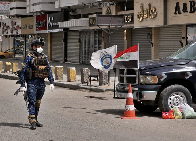 A federal policeman mans a checkpoint near shops that are shuttered to help prevent the spread of the coronavirus, in Baghdad, Iraq, Thursday, March 19, 2020. Iraq announced a weeklong curfew to help fight the COVID-19 pandemic. (Photo by Hadi Mizban/AP Photo)