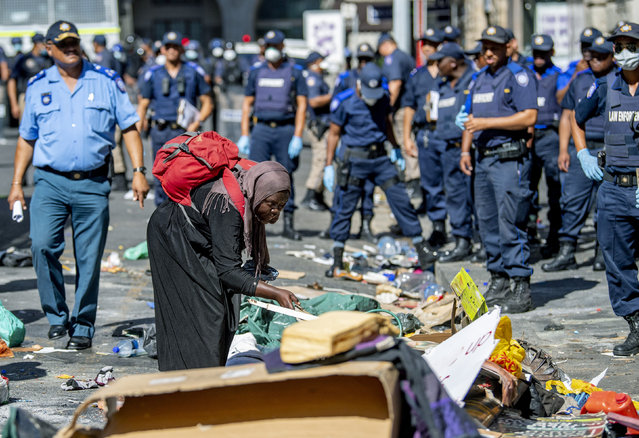 A woman sorts out her belongings, outside the Central Methodist Mission Church in Cape Town, South Africa, Sunday, March 1, 2020 as city officials and police move in to evict them. Hundreds of migrants have been removed from central Cape Town by South African authorities following a months-long stand-off. The migrants removed on Sunday had demanded to be relocated to other countries claiming they had been threatened by xenophobic violence last year. (Photo by AP Photo/Stringer)