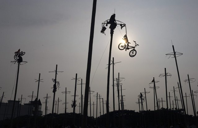 "A participant pulls down a bicycle from the top of a greased pole during the ""Panjat Pinang"" event organised in celebration of Indonesia's 69th Independence Day at Ancol Dreamland Park in Jakarta August 17, 2014. (Photo by Reuters/Beawiharta)"