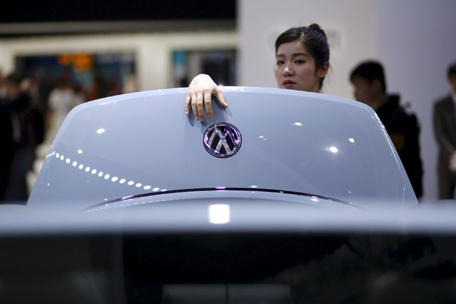 A woman stands next to a Volkswagen car during a presentation at the 16th Shanghai International Automobile Industry Exhibition in Shanghai, in this April 21, 2015 file photo. When China's central bank singled out auto financing companies for extra help on August 25, 2015, it effectively freed up more than 200 million yuan ($30 million) for Volkswagen AG's China finance unit, which it can use to boost falling car sales, a top official said on August 28, 2015. (Photo by Aly Song/Reuters)