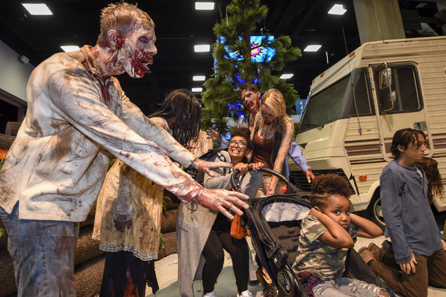 """Fans pose for a photos with zombies at """"The Walking Dead"""" booth during Preview Night at Comic-Con International held at the San Diego Convention Center Wednesday, July 20, 2016, in San Diego. (Photo by [Denis Poroy/Invision/AP Photo)"""