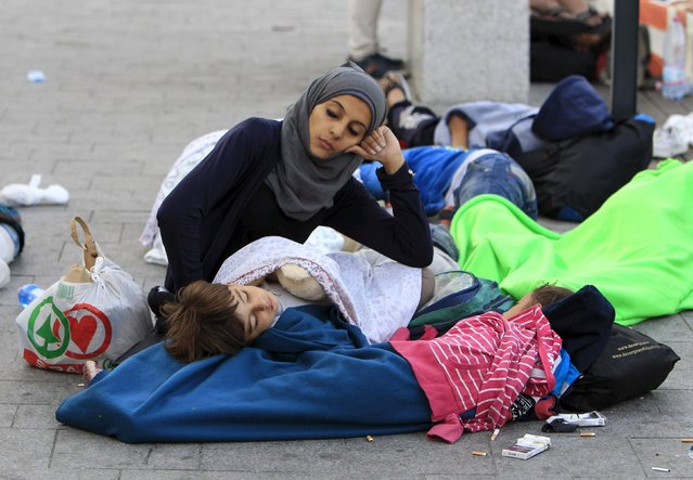 Migrants rest outside the main Eastern Railway station in Budapest, Hungary, September 2, 2015. Hungary closed Budapest's main Eastern Railway station on Tuesday morning with no trains departing or arriving until further notice, a spokesman for state railway company MAV said. Hundreds of angry migrants demonstrated outside the station on Tuesday demanding they be allowed to travel on to Germany, as the biggest ever influx of migrants into the European Union left its asylum policies in tatters. (Photo by Bernadett Szabo/Reuters)