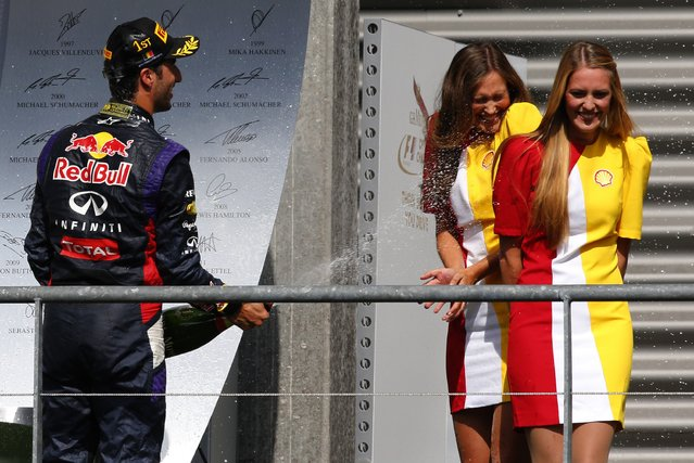 Red Bull Formula One driver Daniel Ricciardo of Australia (L) sprays champagne on hostesses while celebrating his victory in the Belgian Grand Prix in Spa-Francorchamps August 24, 2014. (Photo by Yves Herman/Reuters)