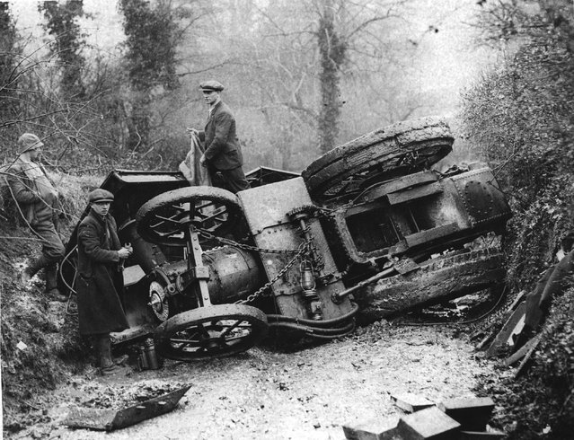 A group of men around an overturned  traction engine in a lane in Winford, Somerset. 26th March 1936. (Photo by Fox Photos)