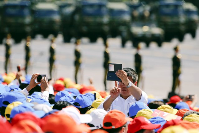A man turns his camera phone towards Chinese President Xi Jinping (not pictured) and other leaders during the military parade marking the 70th anniversary of the end of World War Two, in Beijing, China, September 3, 2015. (Photo by Damir Sagolj/Reuters)