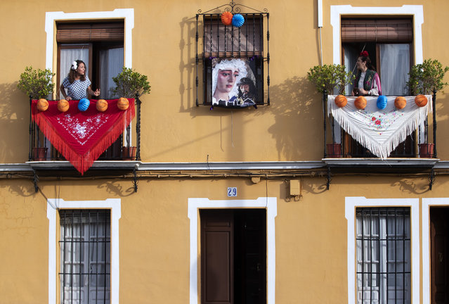 In this photo taken on Thursday April 23, 2020, women in traditional dress sing on their decorated balconies in the village of Mairena del Alcor, some 21 kilometres (13 miles) from Seville during the annual traditional April Fair celebrated across the southern Andulacia Provence. Without breaking the confinement rules and maintaining their distance from each other, the residents of the village have found a novel way of continuing the tradition of the fair which has been cancelled due to the Coronavirus outbreak and normally includes flamenco dancing, bullfighting, eating and drinking. (Photo by Miguel Morenatti/AP Photo)