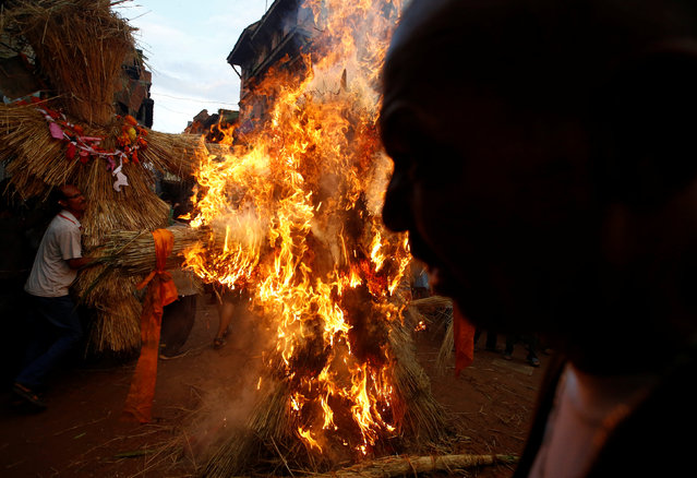 People carry an effigy of demon Ghantakarna (L) as another effigy (C) of the demon is burnt to symbolize the destruction of evil, during the Ghantakarna festival at the ancient city of Bhaktapur, Nepal August 1, 2016. (Photo by Navesh Chitrakar/Reuters)