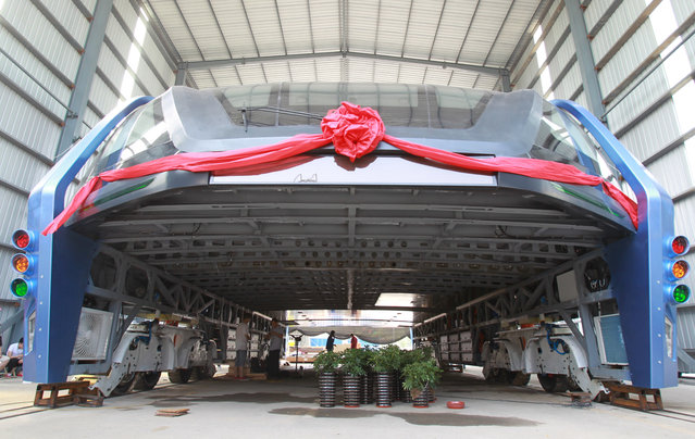 A model of a innovative street-straddling bus called Transit Elevated Bus is seen after a test run in Qinhuangdao, Hebei Province, China, August 3, 2016. Chinese engineers have built a full-sized test model of the much-anticipated TEB-1 straddling bus concept. First revealed in 2010, the bus promises to beat traffic by tiptoeing over it – with wheels at the edges of the road, it acts rather like an enormous tunnel, appearing to swallow the traffic that passes underneath. (Photo by Reuters/Stringer)