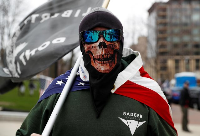 A man wearing a mask poses as demonstrators protest the extension of the emergency Safer at Home order by State Governor Tony Evers to slow the spread of the coronavirus disease (COVID-19), outside the State Capitol building in Madison, Wisconsin, U.S., April 24, 2020. (Photo by Shannon Stapleton/Reuters)