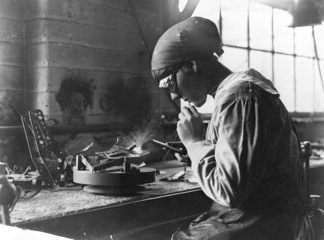 A woman munitions worker welds at a work bench in an armaments factory, 1915. (Photo by Hulton Archive)