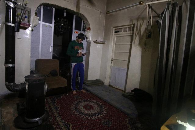 Gymnast Ahmad al-Sawas reads inside his home during a power cut, in the rebel-held Bustan al-Qasr neighbourhood of Aleppo, Syria March 26, 2016. (Photo by Abdalrhman Ismail/Reuters)