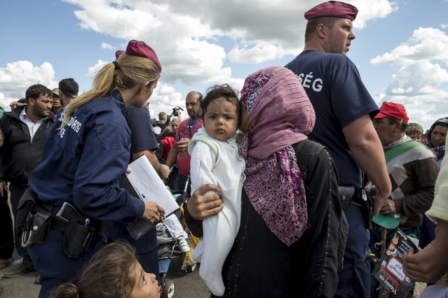 A migrant carries a child as she walks past Hungarian police officers to board a bus at a collection point in the village of Roszke, Hungary, September 7, 2015. (Photo by Marko Djurica/Reuters)