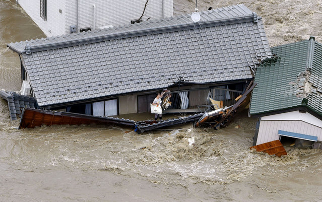 Residents and dogs wait for rescuers as the house is submerged in water flooded from a river in Joso, Ibaraki prefecture, northeast of Tokyo Thursday, September 10, 2015. (Photo by Kyodo News via AP Photo)