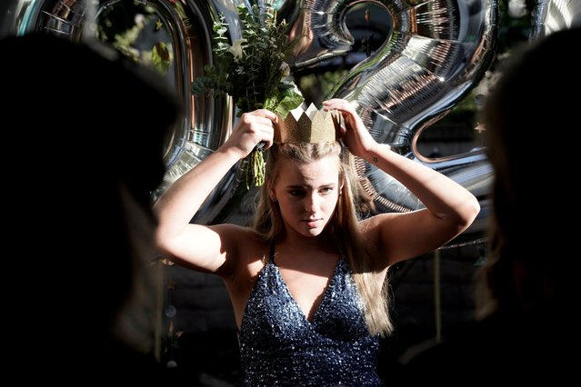 Torrey Pines High School graduating student Phoebe Seip, 18, crowns herself while celebrating her canceled prom night at home during the coronavirus disease (COVID-19) outbreak in San Diego, California, U.S., May 16, 2020. (Photo by Bing Guan/Reuters)