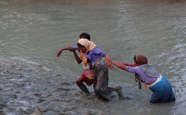 Rohingya refugees help a woman to cross the Naf River as they move across the Myanmar-Bangladesh border in Palong Khali, near Cox's Bazar, Bangladesh on November 1, 2017. (Photo by Hannah McKay/Reuters)