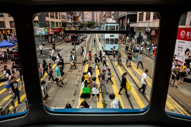 People crossing a road are seen through the window of a tram in Hong Kong on May 23, 2020. A proposal to enact new Hong Kong security legislation was submitted to China's rubber-stamp in Beijing on May 22, state media said, a move expected to fan fresh protests in the semi-autonomous financial hub. (Photo by Isaac Lawrence/AFP Photo)