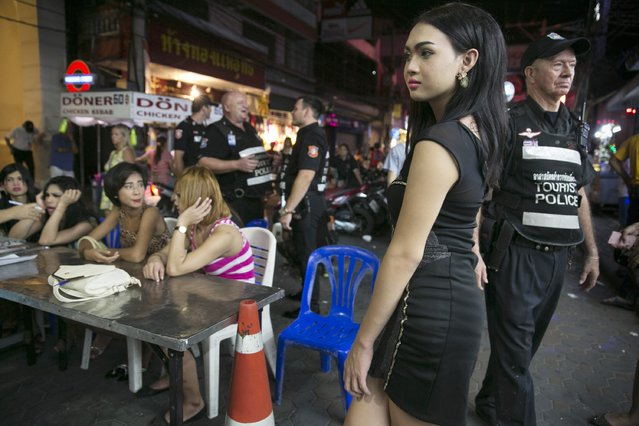 Thai ladyboys are detained while waiting to be taken to the police station September 21, 2014 in Pattaya, Thailand. Pattaya is tackling s*x tourism and crime as the city attempts to clean up it's image doing nightly sweeps in the popular red-light district called the Walking Street. Ladyboy s*x workers are being targeted by police who are assisted by members of the Foreign Tourist Police Assistants (FTPA). They are fined 300 Thai bhat ( almost $10 US). (Photo by Paula Bronstein/Getty Images)