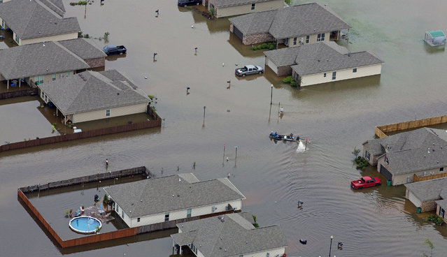 In this aerial photo a boat motors between flooded homes after heavy rains inundating the region Saturday, August 13, 2016, in Hammond, La. Louisiana Gov. John Bel Edwards says more than 1,000 people in south Louisiana have been rescued from homes, vehicles and even clinging to trees as a slow-moving storm hammers the state with flooding. (Photo by Max Becherer/AP Photo)