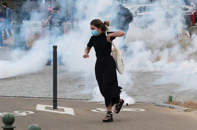 A demonstrator flees from tear gas during a protest, organised by Black Lives Matter Belgium, against racial inequality in the aftermath of the death in Minneapolis police custody of George Floyd, in central Brussels, Belgium on June 7, 2020. (Photo by Yves Herman/Reuters)