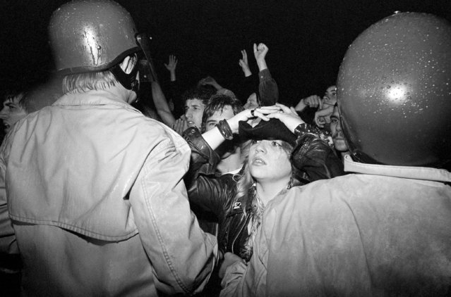 Sixteen-year-old Chris Nygrad, of Worcester, Mass., reacts with tears as she tries to look for members of the Rolling Stones from between a line of police officers on Monday, September 15, 1981 in Worcester, Mass. Nygrad was one of about 4,000 fans who gathered outside a nightclub where the rock group entertained about 300 in a preview of their upcoming U.S. tour. (Photo by Bill Polo/AP Photo)