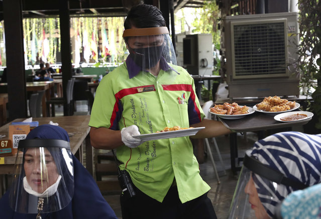 A waiter wearing protective face shield to help curb the spread of the new coronavirus delivers dishes to customers at a seafood restaurant on the outskirts of Jakarta, Indonesia, Wednesday, June 10, 2020. As Indonesia's overall virus caseload continues to rise, Jakarta has moved to restore normalcy by lifting some restrictions this week, saying that the spread of the virus in the city of 11 million has slowed after peaking in mid-April. (Photo by Tatan Syuflana/AP Photo)