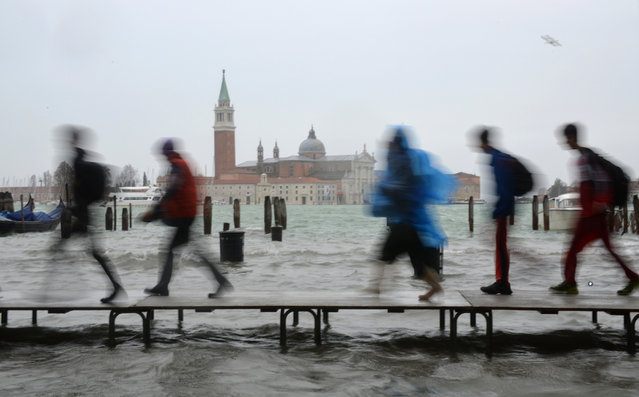 Tourists walk on footbridges during a 'acqua alta' on November 11, 2012 in Venice. Rain and wind hit the north of Italy on Sunday and the folooding reached 150 centimetres in Venice. (Photo by Marco Sabadin/AFP Photo)