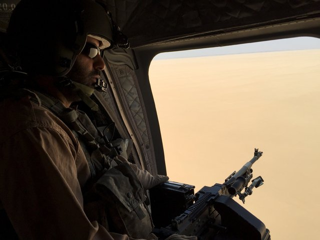 A soldier from the United Arab Emirates armed with a machine gun watches over Yemeni territory on a chinook helicopter flying a small group of journalists to the the frontline conflict zone of Marib in central Yemen September 14, 2015. (Photo by Noah Browning/Reuters)