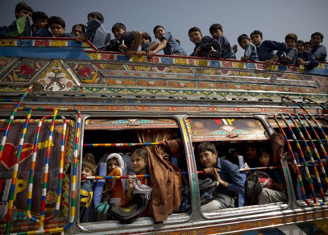 In this Friday, October 4, 2013 file photo, Pakistani children crowd on a bus after being picked up from school in Wajah Khiel, Swat Valley, Pakistan. (Photo by Anja Niedringhaus/AP Photo)