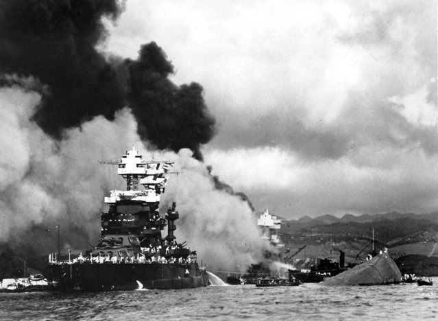 Torpedoed and bombed by the Japanese, the battleship USS West Virginia begins to sink after suffering heavy damage (center) while the USS Maryland (left) is still afloat in Pearl Harbor. The capsized USS Oklahoma is at right. (U.S. Navy/Associated Press)