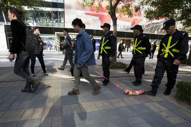 Chinese performance artist Han Bing, left, and his friend Hui Li, center, drag an iPhone and a string of apples, respectively, as they are escorted by security guards in a shopping district where an Apple retail store is located in Beijing, China, Thursday, October 16, 2014. Han Bing, known to take a cabbage out on a walk to raise questions about our attachments to things, hopes to highlight our modern dependence on the mobile phone in this performance. (Photo by Ng Han Guan/AP Photo)