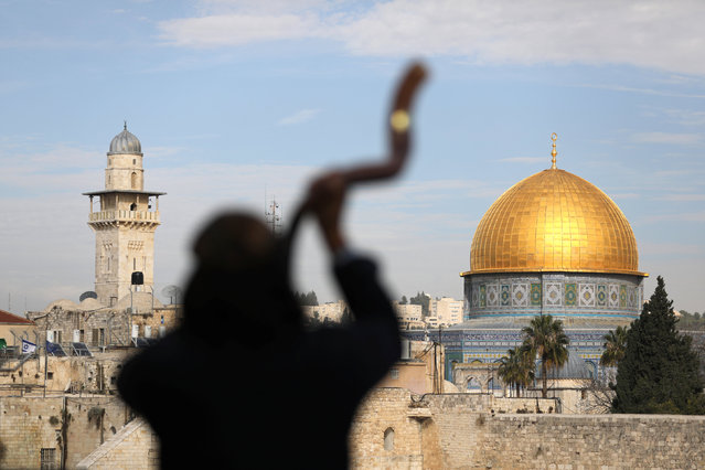 A man is silhouetted while he blows a Shofar, a ram horn, as the Dome of the Rock (R), located in Jerusalem's Old City on the compound known to Muslims as Noble Sanctuary and to Jews as Temple Mount, is seen in the background December 10, 2017. (Photo by Ammar Awad/Reuters)