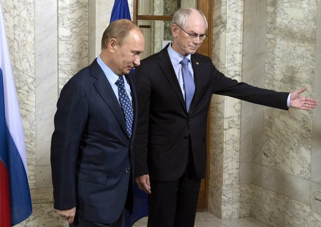 EU Council President Herman Van Rompuy (R) shows the way to Russia's President Vladimir Putin as they meet in Brussels, on December 20, 2012. Putin arrived yesterday in Brussels to take part in a working session of the 30th EU-Russia summit at EU headquarters. (Photo by Sergei Guneyev/AFP Photo/RIA-Novosti)