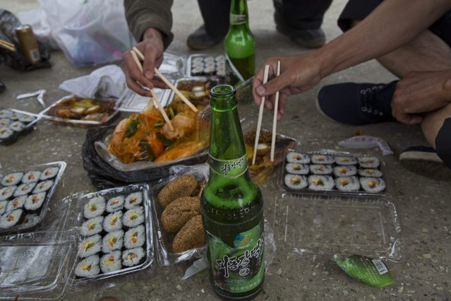 In this June 16, 2014 photo, North Korean men share a picnic lunch and North Korean-brewed and bottled Taedonggang beer along the road in North Korea's North Hwanghae province. (Photo by David Guttenfelder/AP Photo)